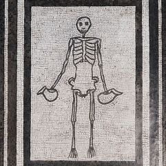 "This Roman mosaic from Pompeii shows a skeleton with jugs, a carpe diem motive (telling us something like ""drink before it is too late""), now in the Museo Archeologico Nazionale in Naples."